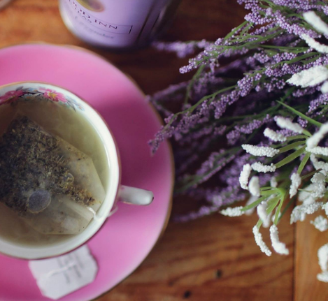 image of cup with herbal tea and white and purple flowers