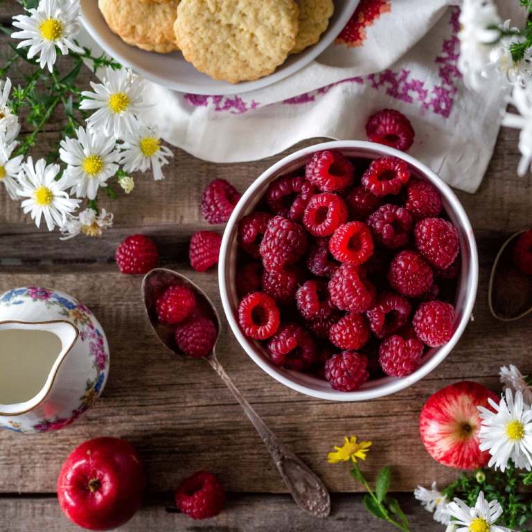 Image of table with raspberries and flowers